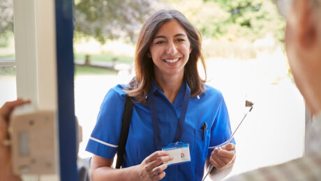 Nurse holding ID card at hospital entrance